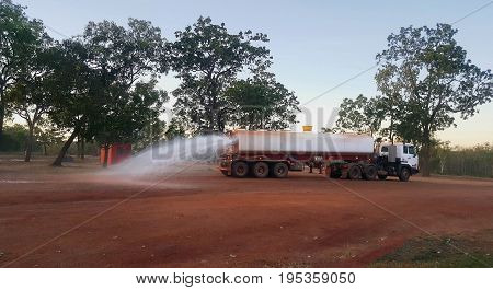 Water truck in the early morning spreading water to keep the dust down