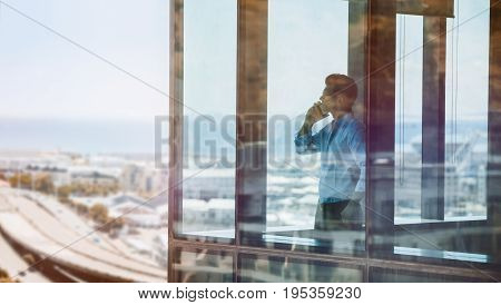 Businessman standing by window and talking on mobile phone. Man standing inside office building and using cell phone.