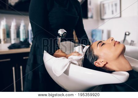 hair stylist drying woman hair with towel in salon. Woman relaxing while the beautician dries the wet hair.