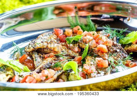 Fried Small Fish With Tomato On A Shiny Plate