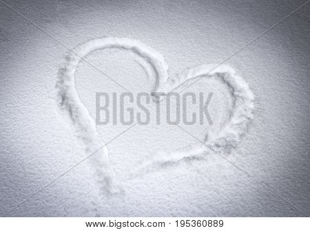 Figure heart in the surface of snow closeup.