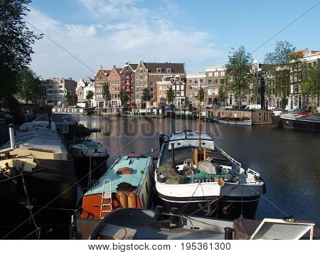 Boats at canal gracht ready to cruise and houses in the morning in capital city of AMSTERDAM in NETHERLANDS HOLLAND in 2015 warm and sunny summer day, Europe on July.