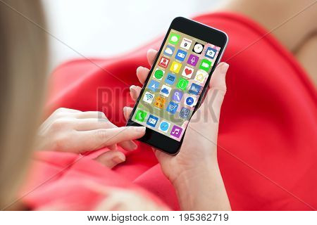 woman in red dress holding touch phone with home screen icons apps