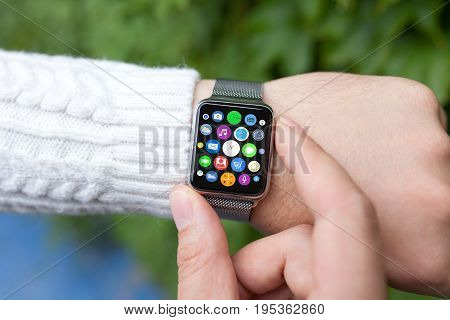 man hand smart touch watch with home screen icons apps on screen