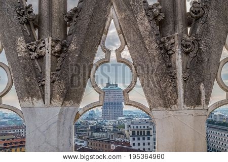 MILAN ITALY - DECEMBER 11 2016: View over Milan from the top of the gothic cathedral Duomo di Milano Italy. Church's roof statues in the foreground skyscrapers of the city in the background.