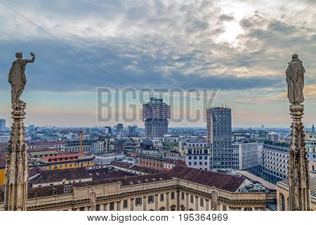 MILAN ITALY - DECEMBER 11 2016: View over Milan from the top of the gothic Milan Cathedral Italy. Church's roof statues in the foreground skyscrapers of the city in the background.