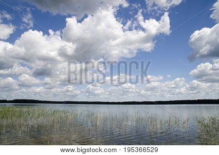 Lake under summer clouds natural background calm lake and deep blue sky landscape
