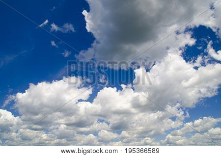Gorgeous white clouds in deep blue summer sky natural background