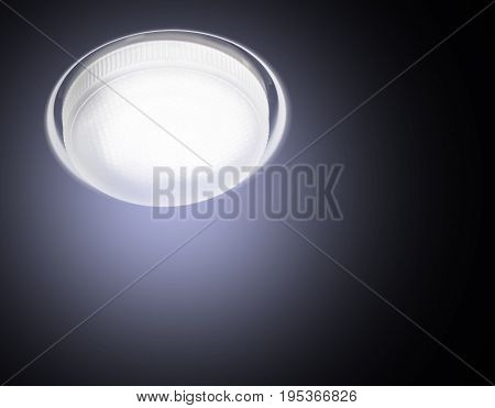 Ceiling Recessed LED lamp is lit close-up cold light on a black background.