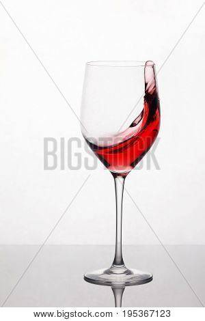 Splashing and moving red wine in the pure wineglass standing against light background with reflection on the stand