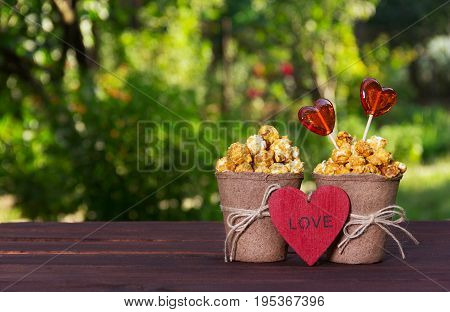 Sweet golden popcorn and lollipops. Set for lovers. Popokorn in a paper bucket and candy hearts. Romantic concept