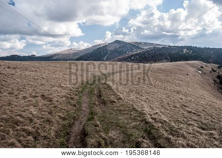 spring in Velka Fatra mountains in Slovakia with mountain meadow hiking trail hills with small snow fields and blue sky with clouds
