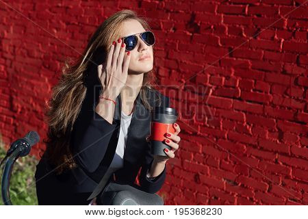 Pretty European female office worker chilling in sunlight wearing sunglasses during coffee break. Caucasian lady enjoying sunny day smiling with happy and carefree look touching her stylish shades.