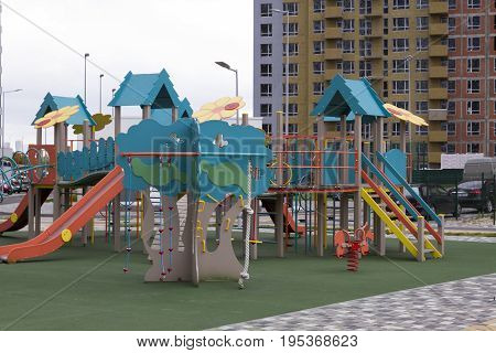 Modern Playground Equipment. Modern Colorful kids playground on yard in the park Against the gray sky