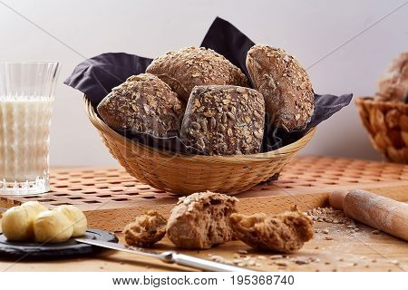 Baked basket with rye buns on wooden table. Rye bread with seeds and glass of milk, close-up.