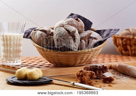 Baked basket with rye buns on wooden table. Rye bread and glass of milk, close-up.