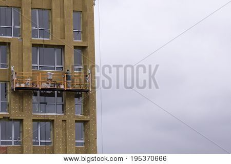 Warming of a high-rise building with mineral wool Against the gray sky
