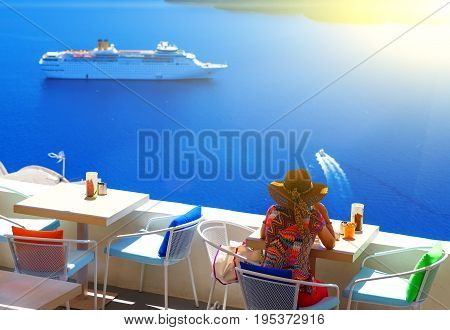 woman in hat sitting in a cafe and enjoys views of the Caldera and cruise ship, Santorini, Fira, Greece