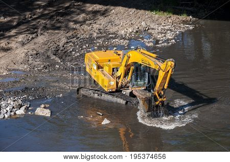 Backhoe working in the River Bernesga, in La Pola de Gordon, Leon Province, Spain on July 14 2014.