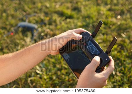 Man holds a drone remote controller in his hands. Quadcopter is on the ground ready to go and fly blurred on the background. No face