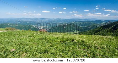 fresh spring mountain meadow on Snilovske sedlo in Mala Fatra mountains in Slovakia with hills on the background and blue sky with few small clouds