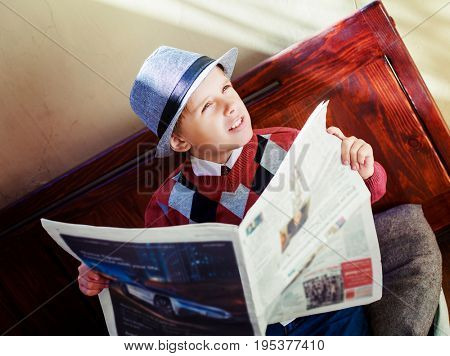 happy stylish boy with a newspaper on the bench