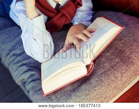 hands of a boy with a book on the bench