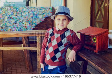 happy boy with retro radio in the street