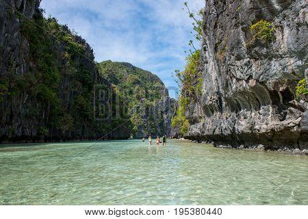 EL NIDO PALAWAN PHILIPPINES - JANUARY 17 2017: Horizontal picture of tourists enjoying sunny day in the exotic Lagoon during island hopping in El nido.