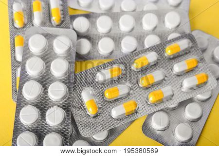 Different pharmaceutical medicaments in brilliant packs on a spacious yellow background. Packs of orange and white antibiotics in organic capsules. Healthcare and medicine concept.