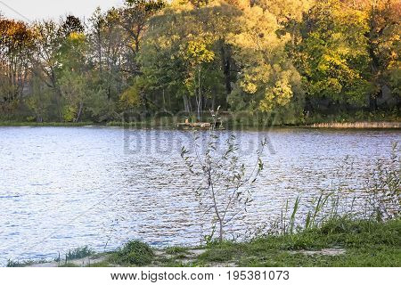 Autumn landscape: beautiful lake with trees on the shore covered with yellow leaves.