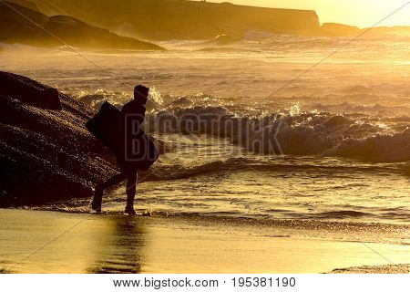 Bodyboarder going into the water at Ipanema tropical sunrise in Rio de Janeiro