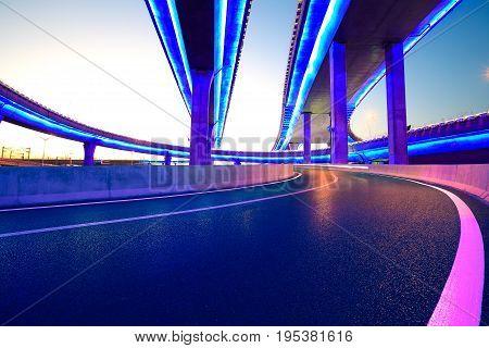 Empty road floor with city overpass viaduct bridge of neon lights night scene poster