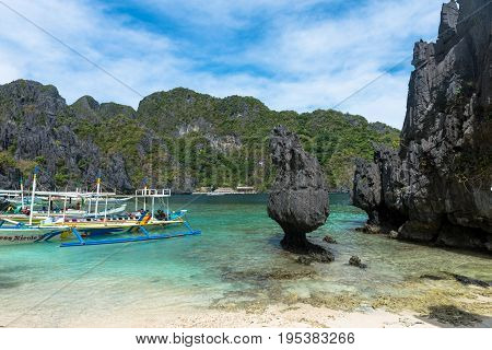 EL NIDO PALAWAN PHILIPPINES - JANUARY 17 2017: Different sharp rocks and a boat that bring tourists in this amazing beach of El Nido.