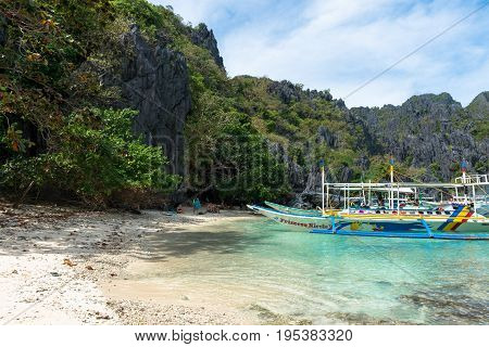 EL NIDO PALAWAN PHILIPPINES - JANUARY 17 2017: Sharp rocks trees boats and the beautiful beach of El Nido's bay.
