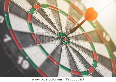dartboard with red dart on target center