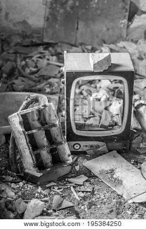 Broken CRT Television Set in abandoned room with many pieces of broken objects and dirt, in black and white