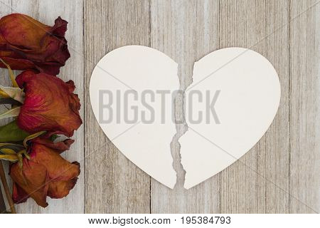 Dead red roses with torn heart-shape card on weathered wood background with copy space for your message