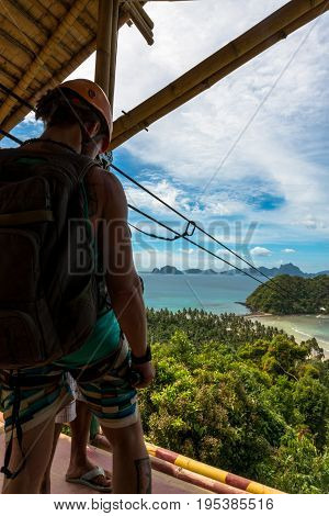 EL NIDO PALAWAN PHILIPPINES - JANUARY 18 2017: Vertical perspective of a tourist waiting to get the zipline to go to Las Cabanas Beach.