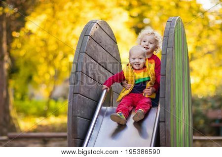 Child On Playground In Autumn. Kids In Fall.