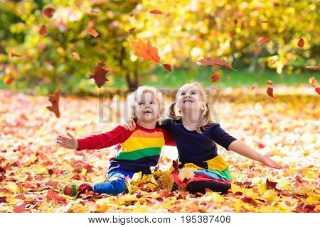 Kids Play In Autumn Park. Children In Fall.