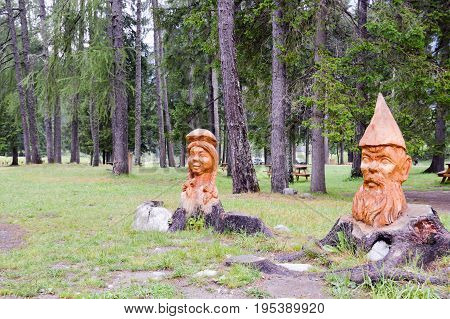 Wooden sculpture of a couple of people of Italian mythology in a natural park in the dolomites in Italy