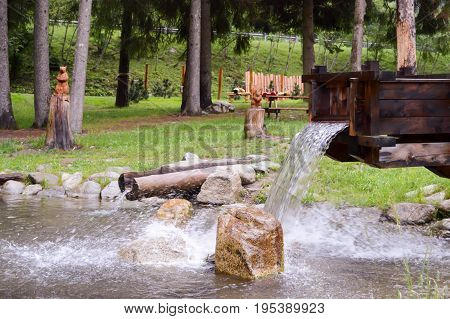 Artificial waterfall In a small pond in a natural park in the dolomites in Italy