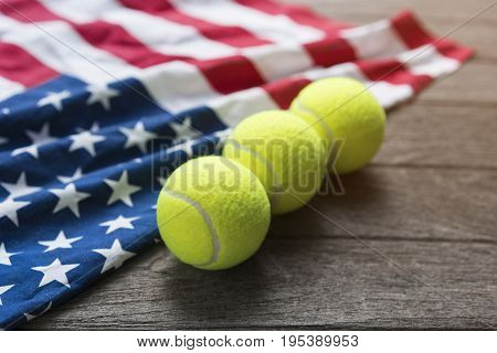 tennis balls with an American flag on wood table
