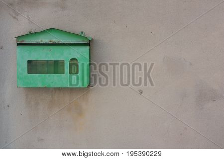 Old green mailbox mounted on a cement wall.