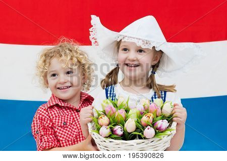 Little Dutch girl and boy wearing traditional national costume dress and hat holding basket of tulips at flag of the Netherlands. Children with souvenirs from Holland. Kids with tulip flowers.
