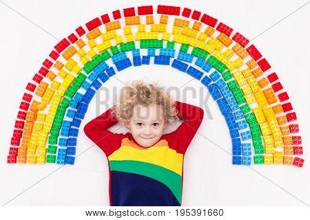 Child Playing With Rainbow Plastic Blocks Toy