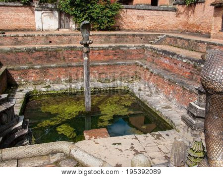 KATHMANDU, BHAKTAPUR, NEPAL. 30 September 2008: Naga Pokhari (Snake Pond) in The Palace of fifty five Windows in Bhaktapur's Durbar Square is a royal water tank encircled by a writhing stone cobra.