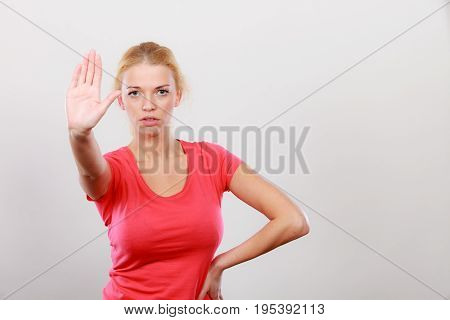 Refusal denial signs. Blonde woman showing stop gesture with open hand refusing something.
