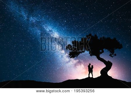 Milky Way with hugging couple under the tree on the hill. Landscape with night starry sky and silhouette of standing man and woman. Milky Way with young people. Space background. Amazing galaxy